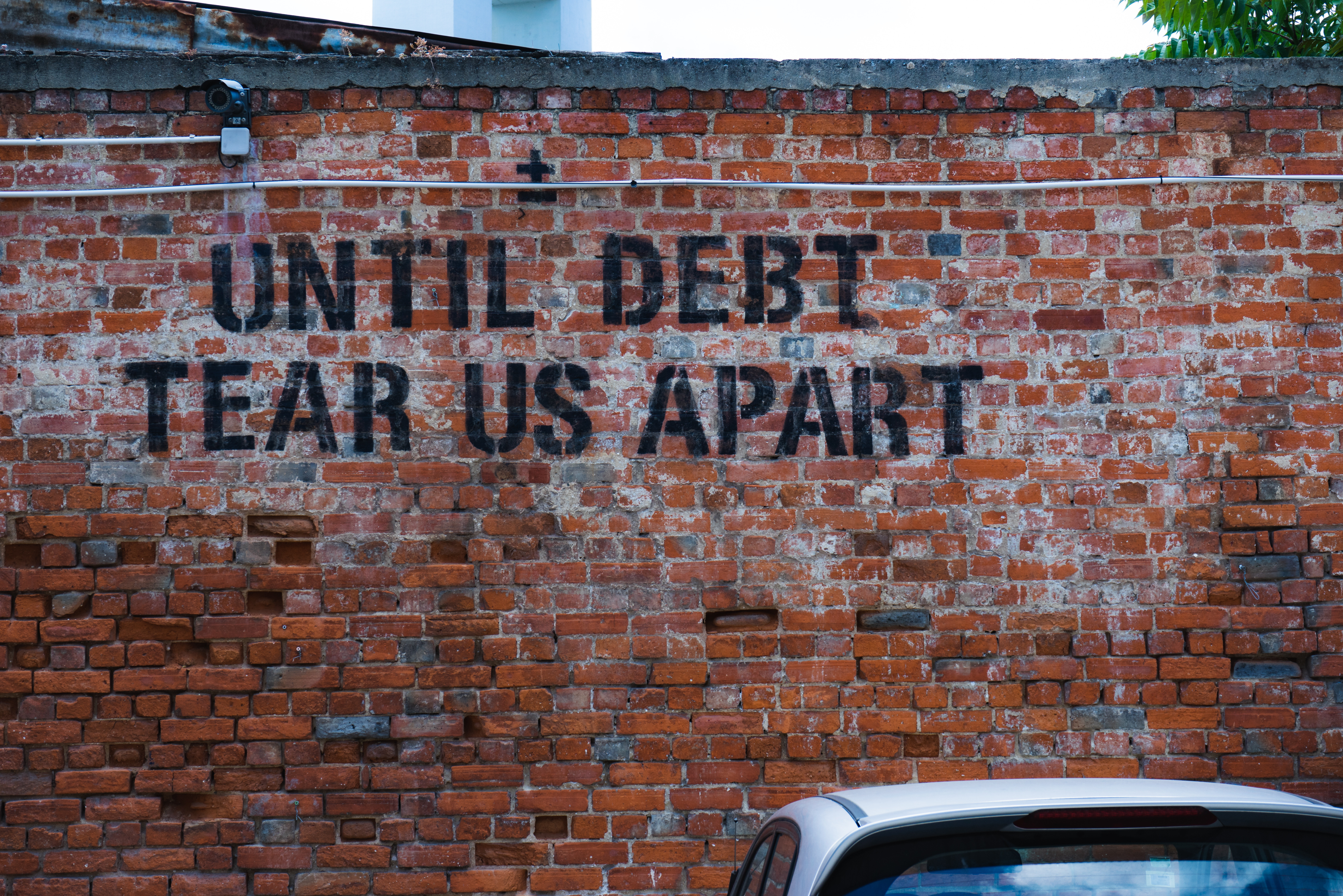 Change Finance -  - Brick wall with writing: Until debt tear us apart